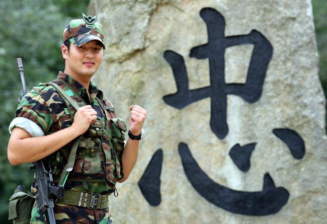 육군27사단 수색대대에서 복무한 김태우가 군 시절 부대 내 기념비 앞에서 주먹을 쥐고 파이팅을 하고 있다.#