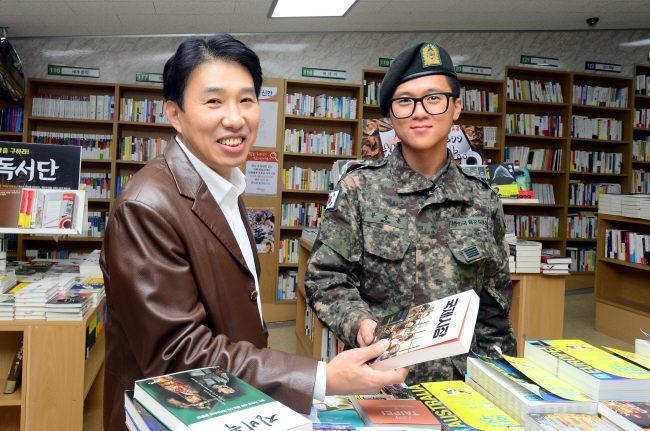 휴가를 나와 서울의 한 서점을 찾은 육군5사단 사자연대 문종훈 병장에게 김호경 작가가 서 '국제시장'을 소개하며 활짝 웃고 있다.