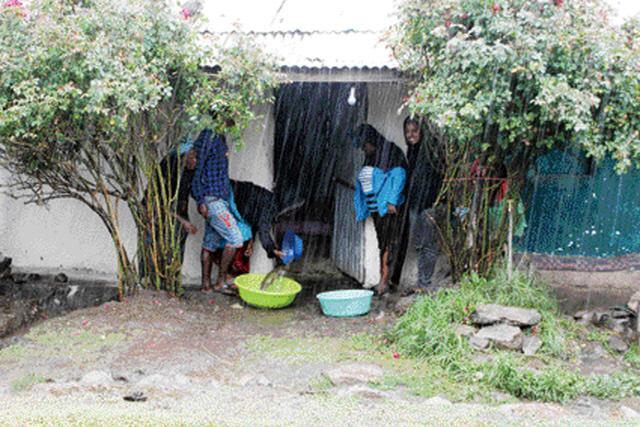 폭우 속에 집이 침수되지 않도록 가족이 빗물을 퍼내고 있는 모습.