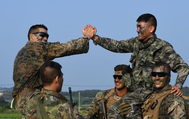 연합기동훈련을 마친 한미 소대장들이 손을 맞잡으며 서로를 격려하고 있다. 사진=양동욱 기자