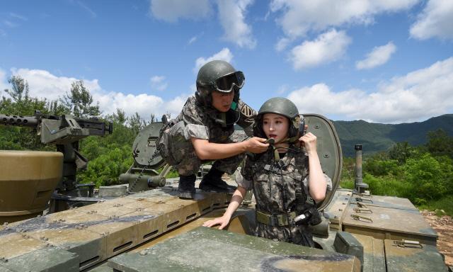기초조종훈련에 참여한 수아가 K2 전차 조종법을 배운 뒤 상판에 탑승해 송수화 수신기 이용방법에 대한 설명을 듣고 있다. 양동욱 기자