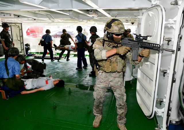 제주기지전대 의무대 장병들이 대테러특수임무대 대원들의 경계 아래 다친 환자에게 응급조치를 하고 있다.  부대 제공