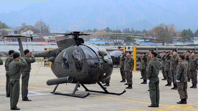육군13항공단 501항공대대에서 열린 500MD 1호기 퇴역식에서 대대 장병들이 1호기를 향해 경례하고 있다.  사진 제공=이상신 PD