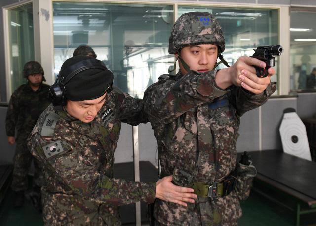 공군16전투비행단 '국군체육부대 전문교관 초빙 사격교육'에서 인천 아시안게임 25m 권총 센터파이어 부문 3위 출신인 권총 전문교관 김진일(왼쪽) 상사가 한 참가자의 사격 자세를 교정해주고 있다.   사진 제공=백승열 상사