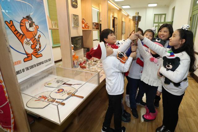 서울 중구 문화역서울284에서 열리는 '두 번의 올림픽, 두 개의 올림픽' 전시장에서 어린이들이 1988 서울올림픽 당시 성화봉을 직접 만져보고 있다.    연합뉴스