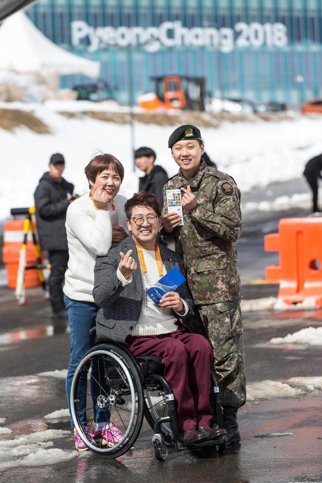호국이 희망 나들이 사업으로 평창 동계 패럴림픽을 관람하게 된 모범병사 황일용 병장이 가족과 함께 하트를 그리며 기념촬영하고 있다. 육군은 '호국이 희망 나들이' 사업을 통해 장애 등으로 군에 간 아들을 면회하기 힘든 가족들을 돕고 있다. 3월에는 평창 패럴림픽 동반관람까지 지원한다.  육군 제공