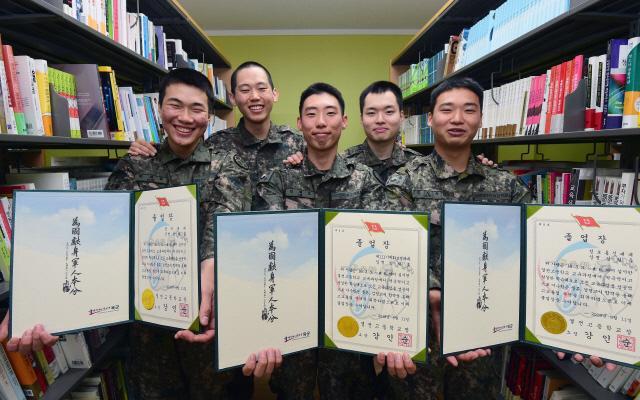 육군20사단 고졸 검정고시 합격 병사들(앞줄)이 결전고등학교 졸업장을 들고 강사 전우들(뒷줄)과 환하게 웃고 있다. 사진=한재호 기자