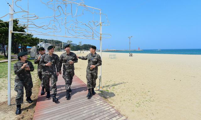 첫 평일 외출 점심식사를 마친 육군8군단 장병들이 후식으로 커피를 마시며 양양 바닷가를 산책하고 있다. 사진=이경원 기자