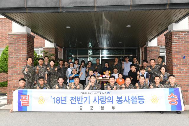 이왕근 공군참모총장과 장병들이 15일 충남 논산시에 위치한 중증 장애인 요양시설인 '성모의 마을'을 방문해 원생들과 기념사진을 찍고 있다.  공군 제공