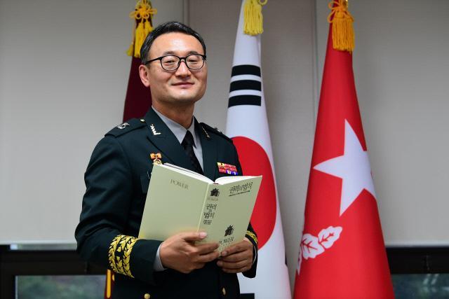 이동호 육군 법무실장이 국방일보 장군의 서재 추천도서인 『권력의 법칙』을 들고 미소를 지어 보이고 있다.