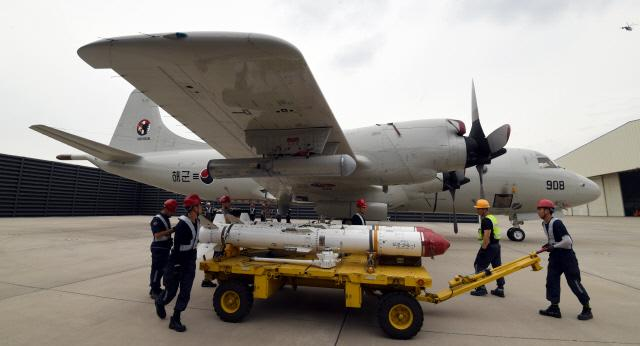 해군6항공전단 항공 무장 부사관들이 대함 유도무기 하푼을 P-3 해상초계기에 장착하기 위해 옮기고 있다.