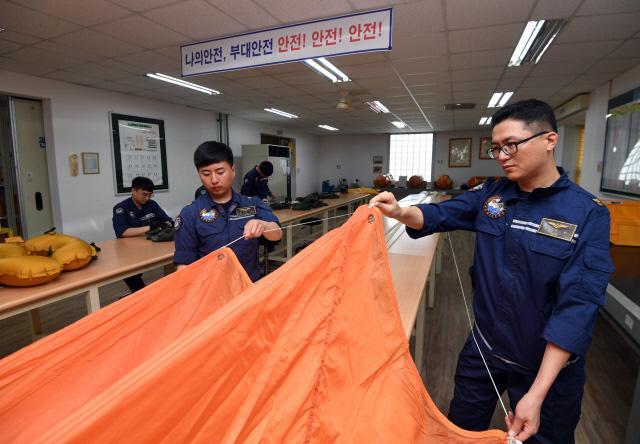 항공 장비 부사관들이 위급 상황에서 승무원의 생환을 도울 낙하산을 점검하고 있다.