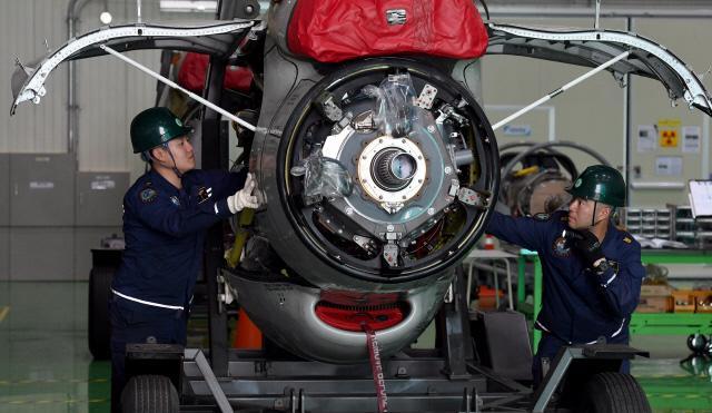 항공 기관 부사관들이 P-3 해상초계기의 '심장'인 엔진을 정비하고 있다.