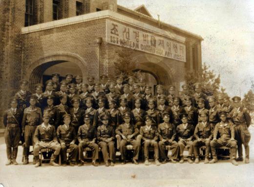 조선경비대 1연대 장병들이 '조선경비대' 현판이 붙은 건물 앞에서 기념사진을 찍는 모습.