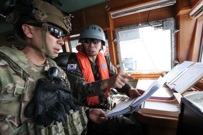 청해부대 28진을 이끌고 있는 이한동(오른쪽) 청해부대장이 우리 상선 피랍 상황을 가정한 전투배치훈련을 하며 함교에서 검문검색대장과 구출작전에 대해 논의하고 있다.