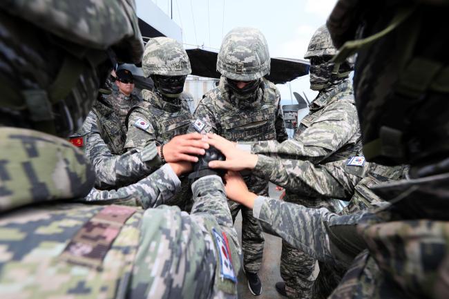 """""""오늘도 완벽… 파이팅""""최영함 경계를 맡은 경계대 해병대원들이 전투배치 훈련 뒤 손을 모아 파이팅을 외치고 있다."""