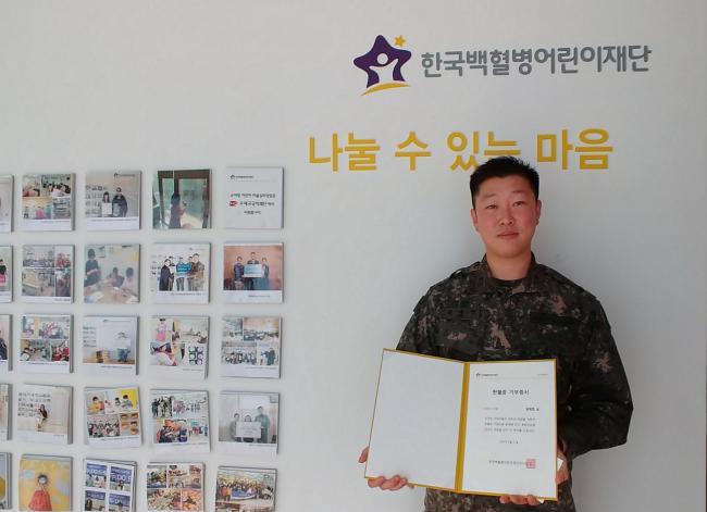 육군53사단 울산연대 김재엽 소령이 한국백혈병어린이재단에 10년간 모은 헌혈증 50장을 기부한 뒤 받은 기부증서를 들어보이고 있다.  부대 제공