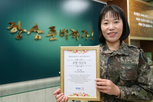 소아함 환자들을 위해 모발을 기증한 육군3군단 헌병단 김현숙 중사가 기증서를 들고 환하게 웃고 있다.  부대 제공