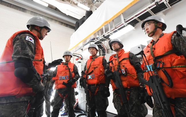 장병들이 승선 검문검색 훈련에 앞서 광주함 헬기 격납고에서 작전 토의를 하고 있다.