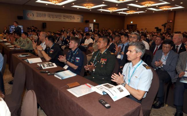 각국의 국방무관을 포함한 콘퍼런스 참석자들이 강연을 들으며 박수 치고 있다.