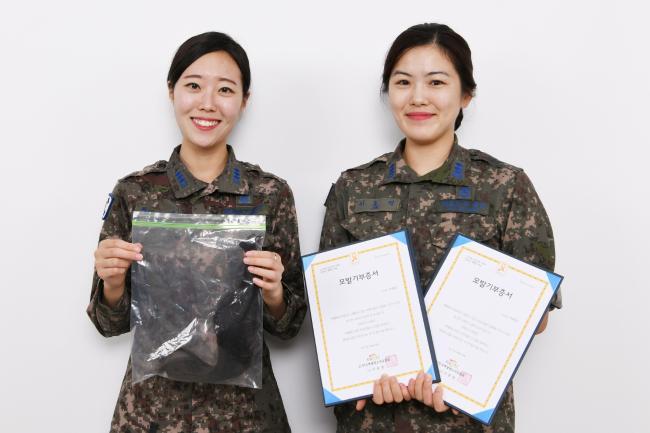 최은비(왼쪽) 대위와 이효정 대위가 각각 기부 예정인 모발과 모발기부증서를 들어 보이고 있다.  부대 제공