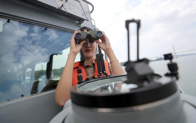 임 홍보위원이 광주함 함교 밖에서 쌍안경으로 해상 목표물을 확인하고 있다.
