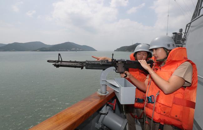 임 홍보위원이 광주함 함교 옆 K6 중기관총 거치대에서 한 수병에게 K6 사격 요령을 배우고 있다.