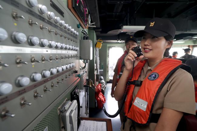 임 홍보위원이 함교에서 방송용 무전기를 통해 함장의 전투배치 명령을 함내에 전파하고 있다.