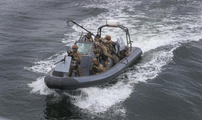 고속단정이 가상의 피랍 선박을 향해 고속으로 기동하는 가운데 검문검색대 공격팀 대원들이 신속한 대응을 위해 경계 및 사격자세를 취하고 있다.