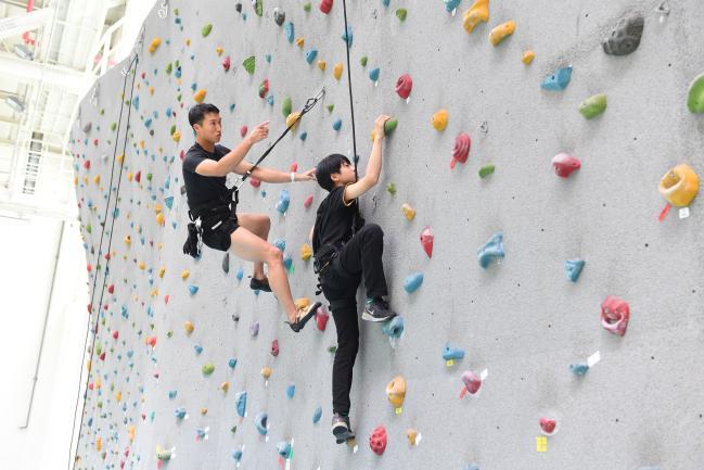 특전사가 여름방학을 맞아 이달 중순까지 운영하는 '군 자녀 클라이밍 교실' 참가 학생이 특전요원의 지도하에 인공암벽을 오르고 있다. 부대 제공