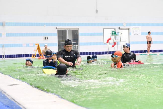 '군 자녀 수영 교실' 참가 학생들이 전문강사 자격을 갖춘 특전요원에게서 수영 기술을 배우고 있다.  부대 제공