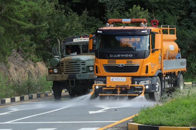 2수송교육연대 면허시험장에서 면허시험이 진행 중인 가운데 살수차가 도로 온도를 낮추기 위해 물을 뿌리고 있다.