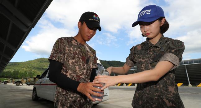 의무요원이 잠시 휴식을 취하고 있는 한 교육생에게 더위를 식힐 얼음을 나눠주고 있다.