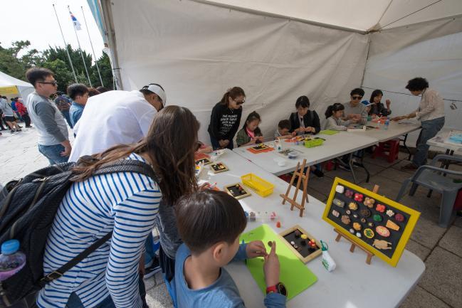 지난해 국립민속박물관에서 마련한 추석 문화행사에 참가한 가족들이 다양한 색깔의 점토로 차례상을 만들어 보고 있다.