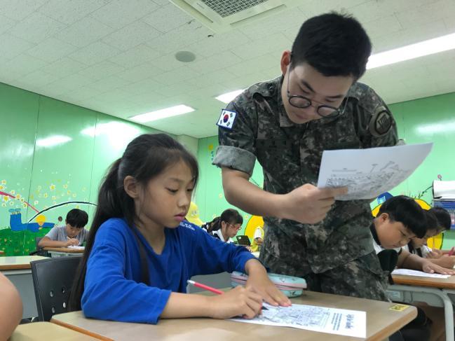 육군8군단 흑곰포병대대 박창대(오른쪽) 병장이 고성 청소년 수련관에서 지역 학생들에게 영어를 가르쳐주고 있다. 부대 제공