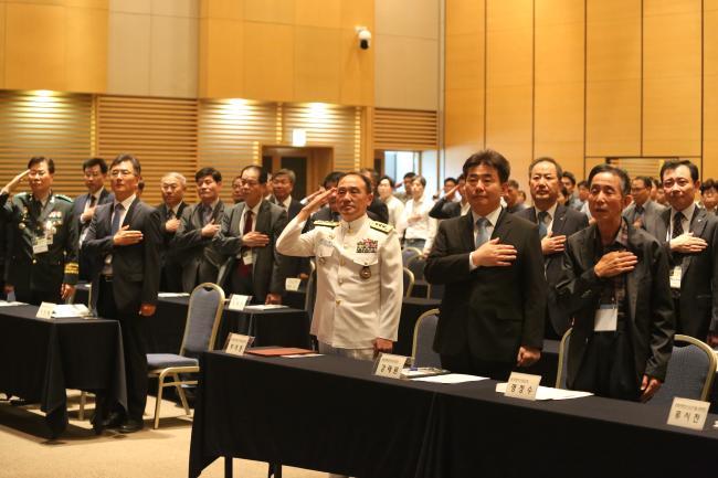 합참과 국방과학연구소, 한국전자파학회가 19일 대전컨벤션센터에서 개최한 '2019 전자전 워크숍 및 전시회'에서 참석자들이 국기에 대한 경례를 하고 있다.  합참 제공