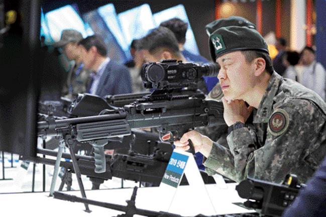 지난 15일 개막한 '서울 국제 항공우주 및 방위산업전시회(ADEX) 2019'가 19일부터 '일반 관람일'로 전환된다. 사진은 ADEX 행사장을 찾은 한 육군 장교가 K15 경기관총을 기반으로 제작한, 경량화된 7.62㎜ 기관총을 살펴보는 모습. 성남=조종원 기자