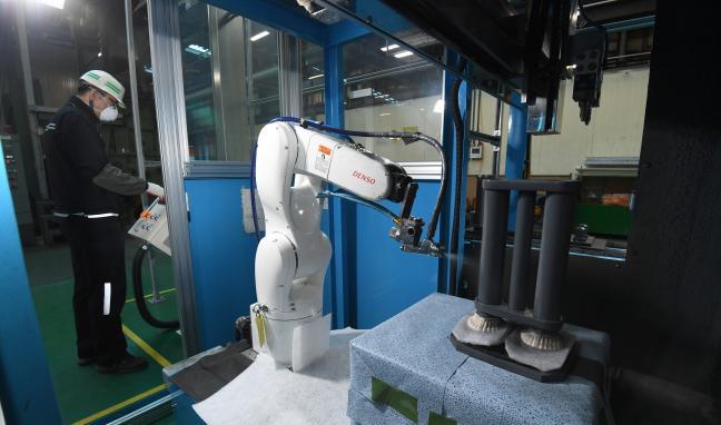 24일 경상남도 창원시 육군군수사령부 종합정비창 궤도 생산공장에서 올해 최초로 도입된 협동로봇이 궤도 보디 접착제 도포 작업을 하고 있다. 궤도 보디 접착제 도포는 로봇 도입 전에는 정비요원 5명이 필요한 작업이었다.  창원=조용학 기자