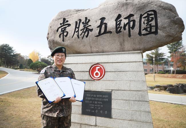 소아암 환자들을 위해 모발을 기증한 육군5사단 신진희 소령(진)이 기증서를 들고 환하게 웃고 있다.  부대 제공