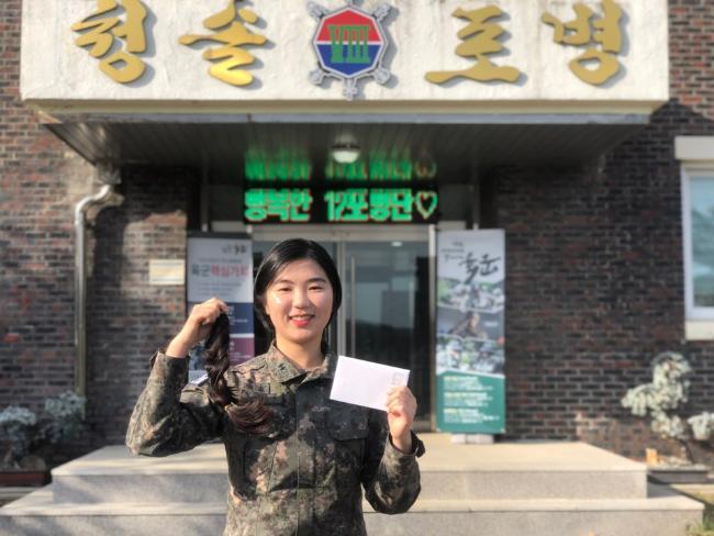 육군8군단 12포병단 임다은 중위가 최근 어린 소아암 환자에게 기부할 자신의 모발과 직접 쓴 편지를 들어 보이며 기념사진을 찍고 있다.  부대 제공