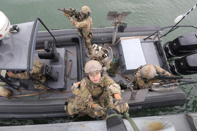 해군2함대 5특전대대 훈련체험에 나선 임미소 국방홍보원 홍보위원이 줄사다리를 이용해 고속단정에서 청주함에 오르고 있다. 조종원 기자