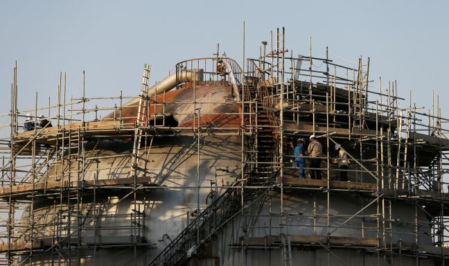 지난해 9월 무인기(드론) 공격을 받아 파괴된 사우디아라비아 국영 석유회사 아람코의 석유 처리 시설을 수리하고 있는 모습. 중동은 올해에도 테러, 내전 등으로 혼란이 계속될 전망이다.    연합뉴스