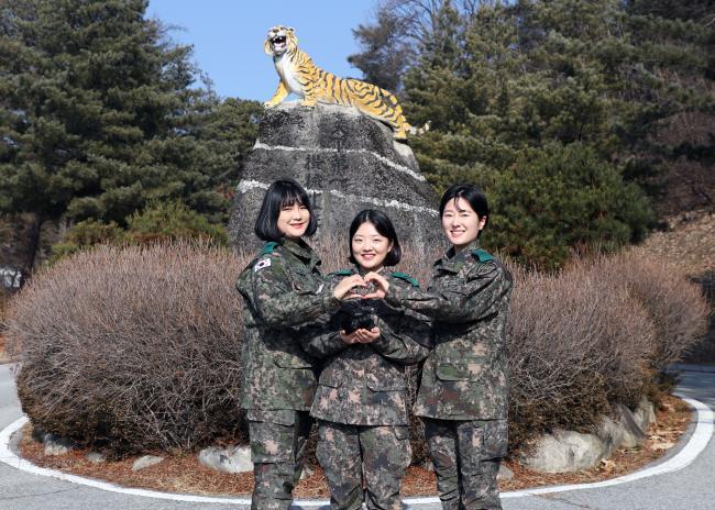 육군수도기계화보병사단 박하늘·박아라 중사, 김윤아 중위(왼쪽부터)가 소아암 환우들에게 기증할 머리카락을 들고 손 하트를 그리며 기념사진을 찍고 있다.  부대 제공