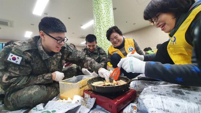 22일 충북 영동군 여성회관에서 육군8탄약창 장병들이 자원봉사자들과 함께 지역 소외계층에게 나눠 줄 음식을 만들고 있다.  부대 제공