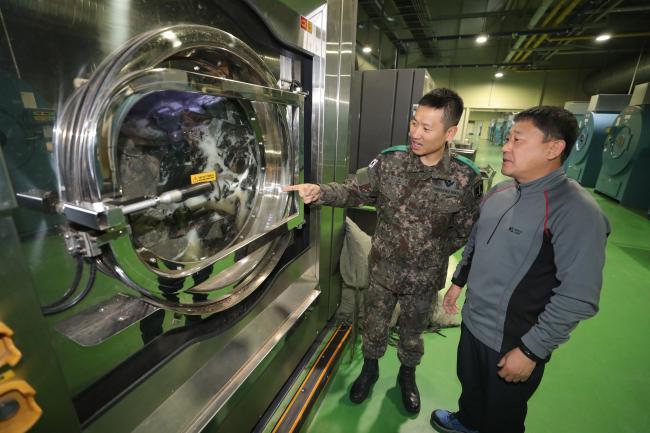 충남 논산 육군훈련소 크린센터에서 보급대장 현성민(왼쪽) 소령이 민간근로자와 함께 가동 중인 세탁기를 점검하고 있다.    사진=조종원 기자