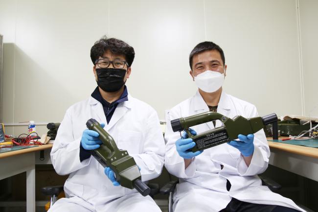육군1군수지원사령부 박주형(왼쪽) 군무주무관과 김재우 중사가 항온항습처리된 클린룸에서 정비가 완료된 K-cam2를 들고 웃고 있다.  부대 제공