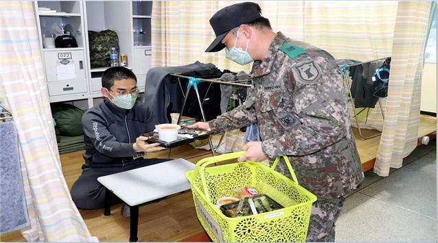 육군32사단에 마련된 임시훈련소에서 교관이 훈련병에게 도시락을 전달하고 있다. 사단은 매끼 취사병들이 직접 조리한 음식을 임시훈련소 대구·경북지역 훈련병들에게 일일이 포장해 전달했다.      부대 제공