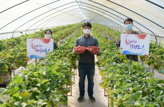 공군18전투비행단 장병들이 부대 인근 농가를 방문해 딸기를 구매한 뒤 농민과 함께 코로나19 극복 응원메시지를 전하고 있다.   사진 제공=고태호 상사
