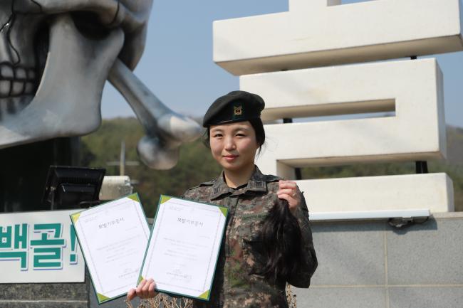 육군3사단 박선혜 중사가 소아암 환아들에게 기부할 머리카락과 앞선 두 번의 모발 기부 후 받은 기증서를 들고 기념사진을 찍고 있다.  부대 제공