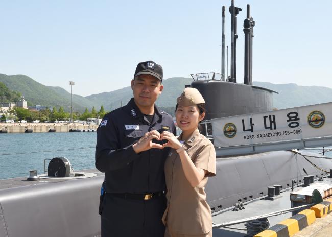 해군 부부 군인 김범준(왼쪽)·윤다정 대위가 21일 부부의 날을 맞아 기념사진을 찍고 있다.  부대 제공